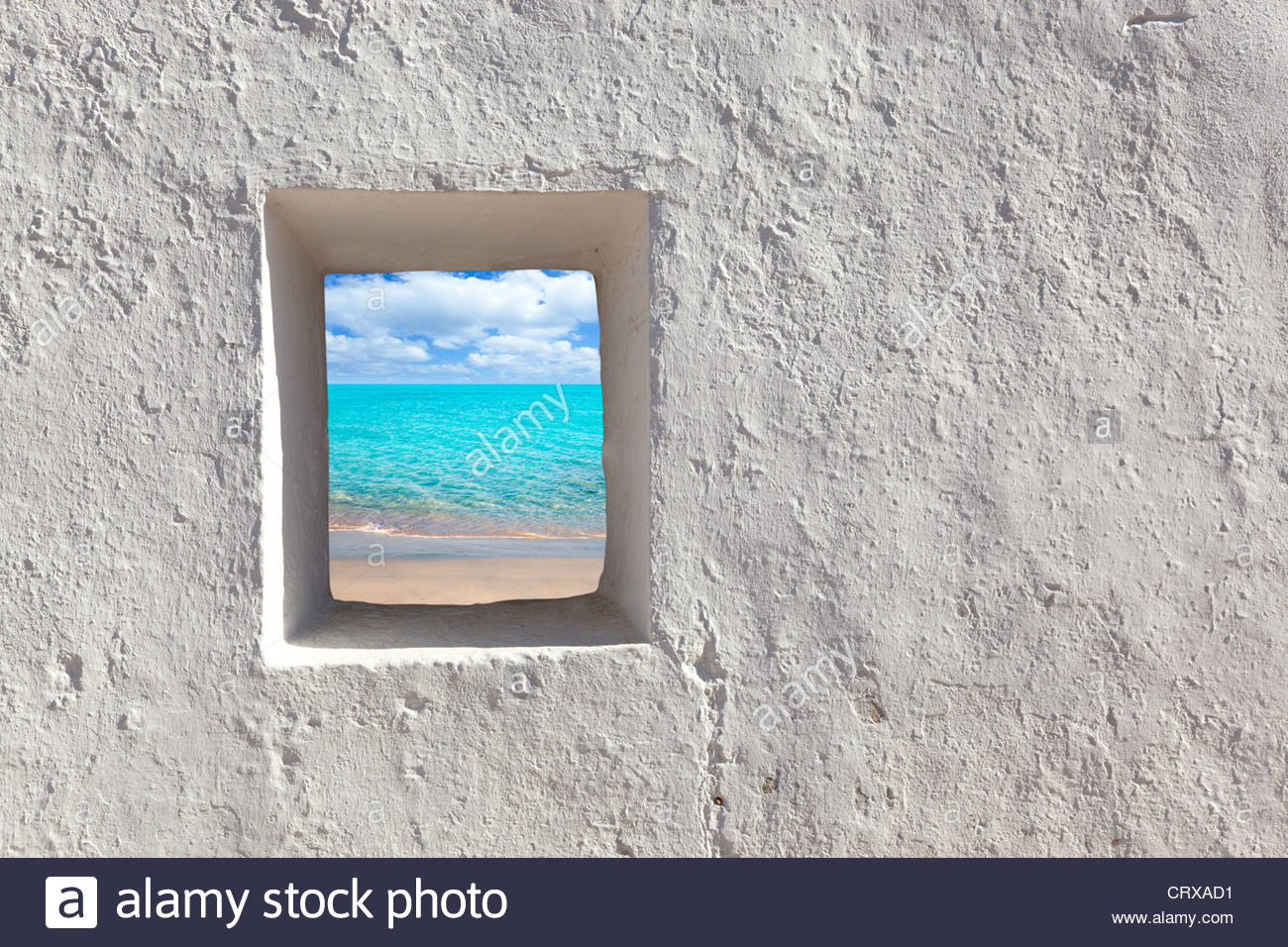Balearic islands idyllic turquoise beach view through whitewashed house open door - Stock Image