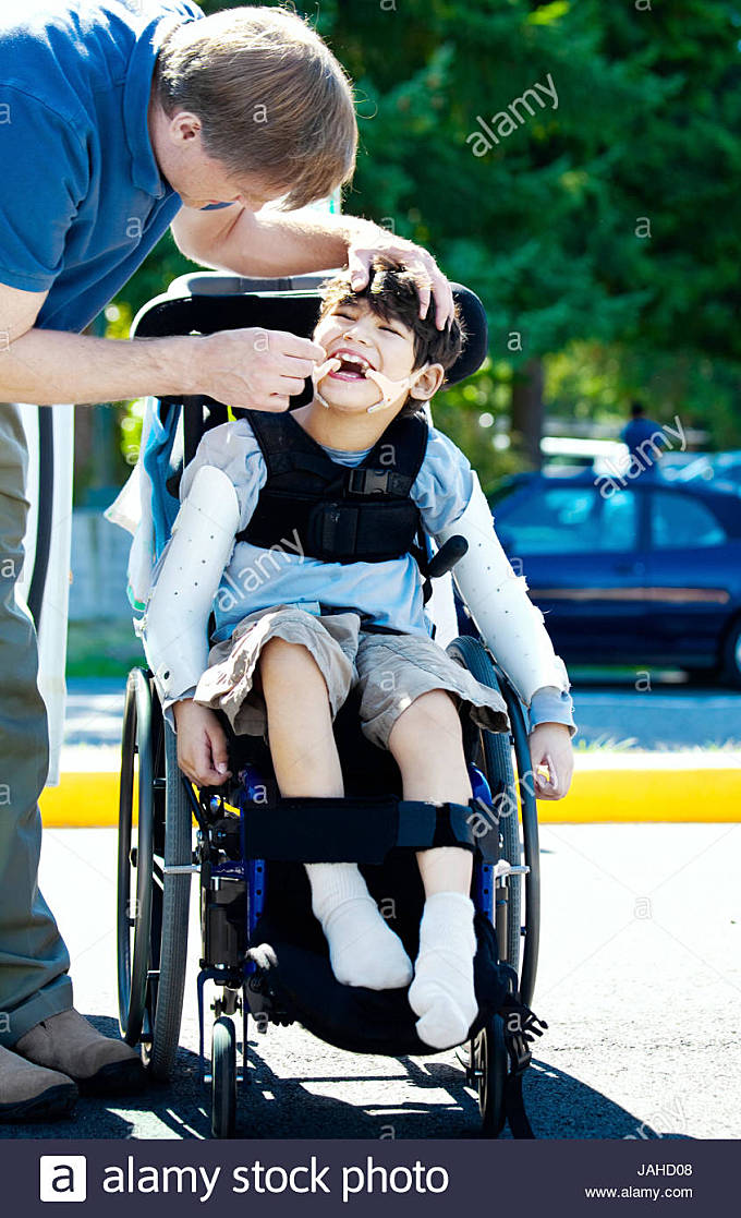 Father helping disabled child in wheelchair. Child has cerebral palsy. - Stock Image