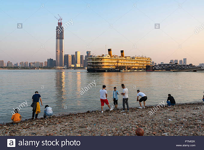 4 October 2018, Wuhan China : people on Yangtze riverbank and Zhiyin Hao cruise boat and Wuhan skyline in background - Stock Image