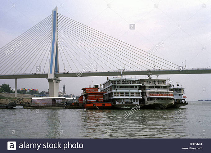 Tour boats moored under the Dragon bridge over Yangtze river in Yichang city Hubei province China - Stock Image