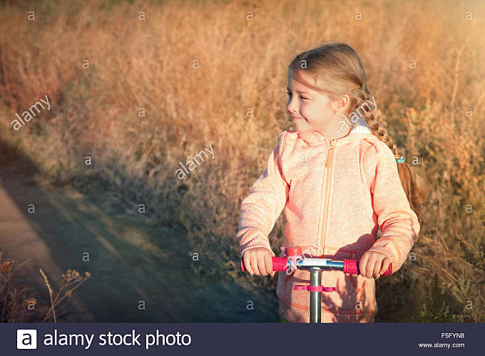 Beautiful girl driving scooter on rural road - Stock Image